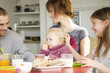 Couple and 2 children at breakfast table