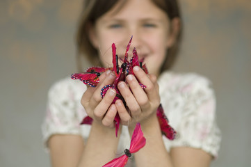 Little girl holding butterfly garland, close-up