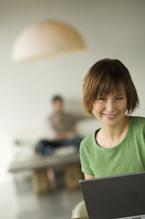 Smiling woman using laptop computer, man in the background