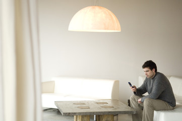 Man sitting on a sofa in living-room, using mobile phone