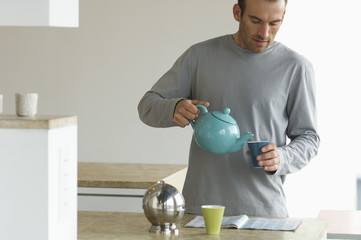 Man standing in the kitchen, pouring tea into a glass
