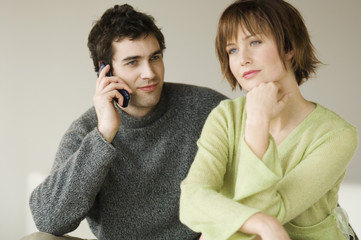 Couple sitting in living-room, man using a mobile phone