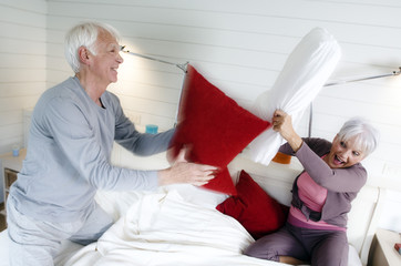 Senior couple having a pillow fight on a bed