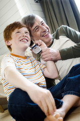 Smiling senior man and boy using a mobile phone