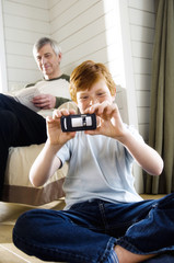 Boy sitting cross-legged, taking picture with camera phone, senior man reading in background