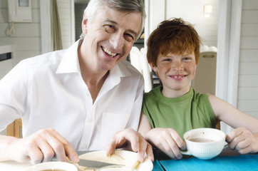 Senior man and boy having breakfast, smiling for the camera