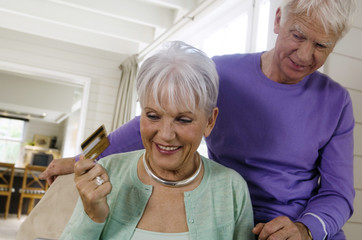 Senior couple inthe living-room, woman holding credit card