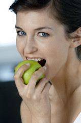 Portrait of a young woman eating an apple