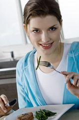 Young woman eating meat and string beans