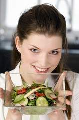 Portrait of a young smiling woman holding mixed salad