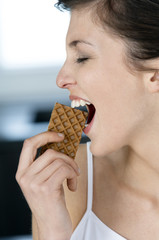 Portrait of a young woman eating a wafer