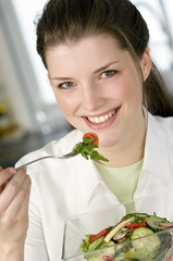 Portrait of a young smiling woman eating mixed salad