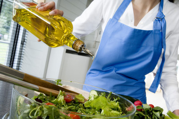 Woman pouring olive oil into a salad, close-up
