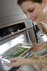 Young woman putting string beans into an oven