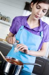 Young woman salting tomato sauce