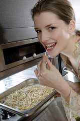 Young woman eating bean sprouts coming out of the oven