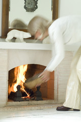 Woman putting log on hearth