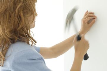 Woman hammering a nail