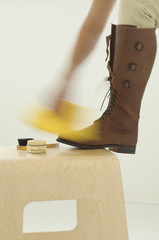 Woman polishing boots, close-up