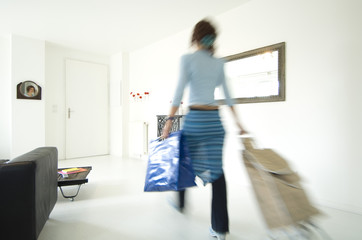 Woman carrying a bag and a shopping trolley in a living-room