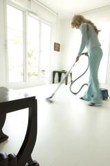 Woman vacuuming in living-room