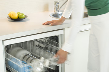 Woman filling dishwasher, close-up
