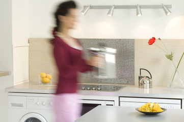 Woman in the kitchen carrying a steam cooker