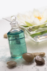 Essential oil bottle, peebles and water lily flower, close-up