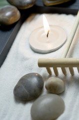 Candle, peebles and rake in zen garden, close-up