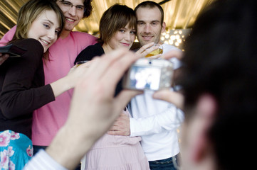 Man taking picture of 2 smiling couples
