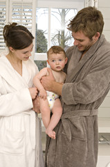 Young couple in bathrobe with baby in bathroom