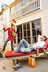 Young woman with cleaning accessories shouting at man lying on a deck chair