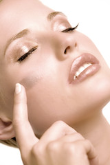 Woman putting make-up base on her cheek, shut eyes, indoors (studio)