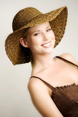 Portrait of a young woman smiling, looking at the camera, brown top, straw hat, indoors (studio)