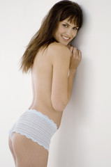 Young smiling woman in panties, leaning against wall
