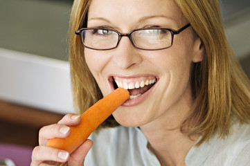 Portrait of a woman biting carrot