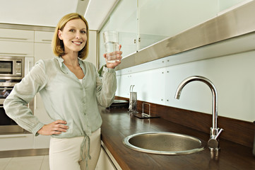 Smiling woman holding glass of water