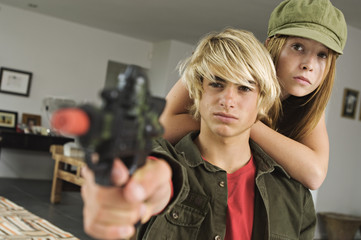 Teenage girl and boy aiming fake handgun