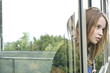 Thinking teenage girl at window