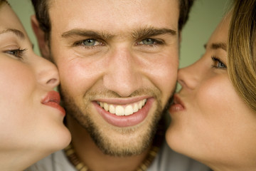2 young women kissing smiling man