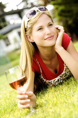 Young woman lying on grass, glass of wine