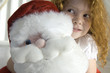 Christmas day, portrait of a little girl holding a cuddly toy (Santa Claus), indoors