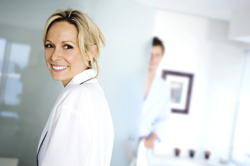 Portrait of a young woman smiling, looking at the camera, man in background, indoors