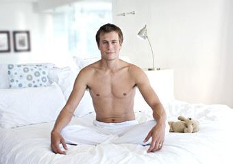 Young man sitting cross-legged on a bed, indoors