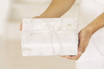 Man hand holding a present, close-up, indoors