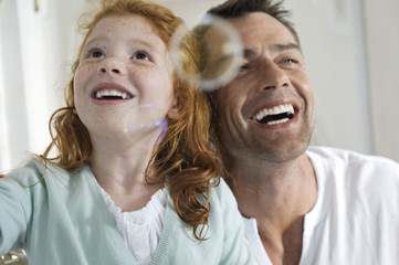 Portrait of father and daughter laughing, looking at soap bubbles, indoors