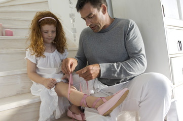 Father and daughter opening Christmas presents, girl holding a princess costume, indoors