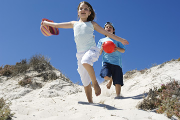 Two children running on the beach, outdoors