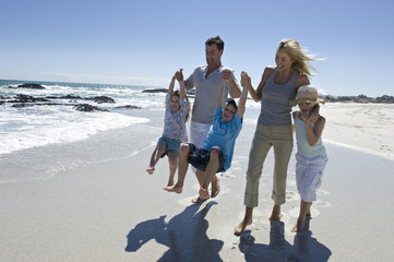 Parents and three children walking on the beach, outdoors