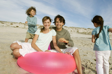 Parents and two children on the beach, couple posing for the camera, outdoors